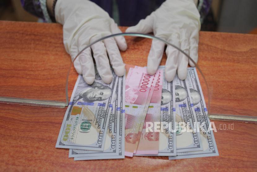 Petugas menunjukkan uang rupiah dan dolar AS di salah satu gerai penukaran mata uang asing. ilustrasi