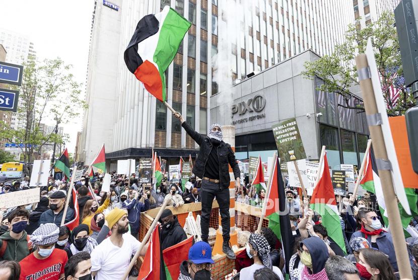Pengunjuk rasa mengibarkan bendera Palestina selama demonstrasi pro-Palestina di dekat Konsulat Jenderal Israel di New York, New York, AS, 11 Mei 2021.