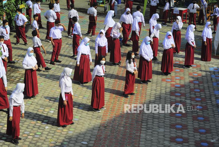 Pemerintah sedang mempertimbangkan dibukanya kembali sekolah tatap muka. Foto, sejumlah siswa berjemur dalam pengawasan guru di halaman sekolah sambil mengenakan masker . (ilustrasi)
