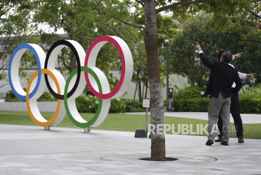 Pria memberi isyarat di dekat Cincin Olimpiade Rabu, 2 Juni 2021, di Tokyo.