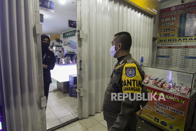Petugas Satpol PP memberikan imbaun agar segera menutup toko saat operasi pembatasan jam operasional di Sawangan, Depok, Jawa Barat, Selasa (22/6/2021). Pemerintah Kota Depok memberlakukan pembatasan jam operasional terhadap pusat perbelanjaan, restoran, dan pertokoan hingga pukul 19.00 WIB dan aktivitas warga hingga pukul 21.00 WIB guna mencegah penyebaran COVID-19.