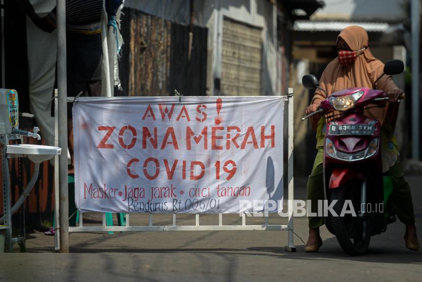 Warga beraktivitas di zona merah Covid-19 Jalan Madrasah RT 006 RW 001, Gandaria Selatan, Cilandak, Jakarta Selatan, Selasa (22/6). Kawasan tersebut memberlakukan mikro lockdown setelah sebanyak 17 warga dinyatakan positif Covid-19 yang diduga berasal dari klaster mudik.