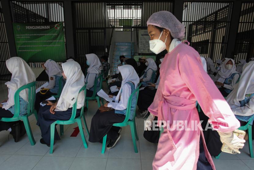 Sejumlah pelajar SMP Negeri 60 Surabaya mengantre untuk tes usap PCR di SMP Negeri 60 Surabaya, Jawa Timur, Selasa (28/9/2021). Dinas Kesehatan Kota Surabaya melakukan tes usap PCR kepada 965 pelajar, sejumlah guru serta tenaga pendidik di sekolah tersebut sebagai upaya antisipasi penyebaran COVID-19 menyusul akan dimulainya pembelajaran tatap muka terbatas di tempat itu.