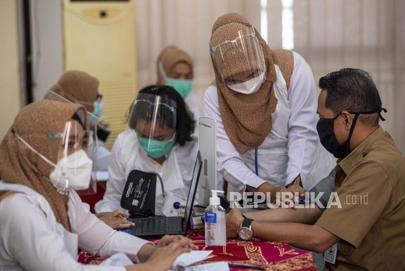 Petugas kesehatan memeriksa tensi sebelum penyuntikkan vaksin kepada tenaga pendidikan di Palembang, Sumatra Selatan, beberapa waktu lalu.