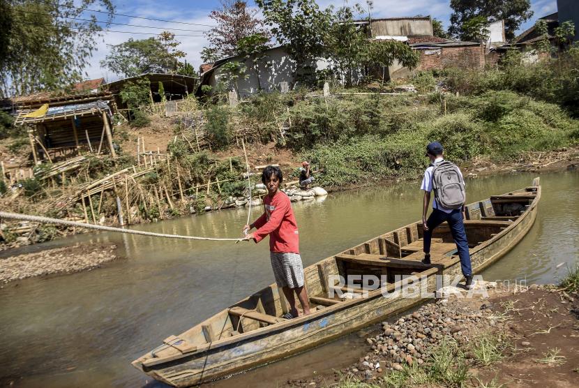 Seorang pelajar menaiki perahu eretan untuk menyeberangi sungai Citarum di Desa Talun, Kecamatan Ibun, Kabupaten Bandung, Rabu (22/9). Warga di daerah tersebut masih memanfaatkan jasa penyeberangan perahu eretan untuk mempersingkat jarak tempuh dan waktu dengan tarif Rp1000 hingga Rp2000.