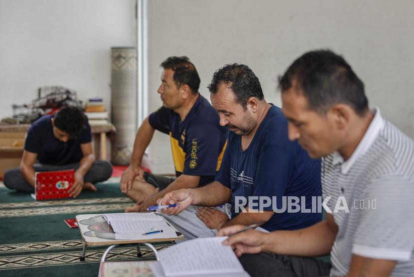 Pengungsi Hazara dari Afghanistan yang telah menunggu untuk dimukimkan kembali ke negara ketiga selama bertahun-tahun, menghadiri kelas bahasa Inggris di dalam musala atau musholla di bekas fasilitas militer yang diubah sebagai tempat penampungan sementara untuk pengungsi di Jakarta, Indonesia, 07 September 2021 (dikeluarkan 13 September 2021).