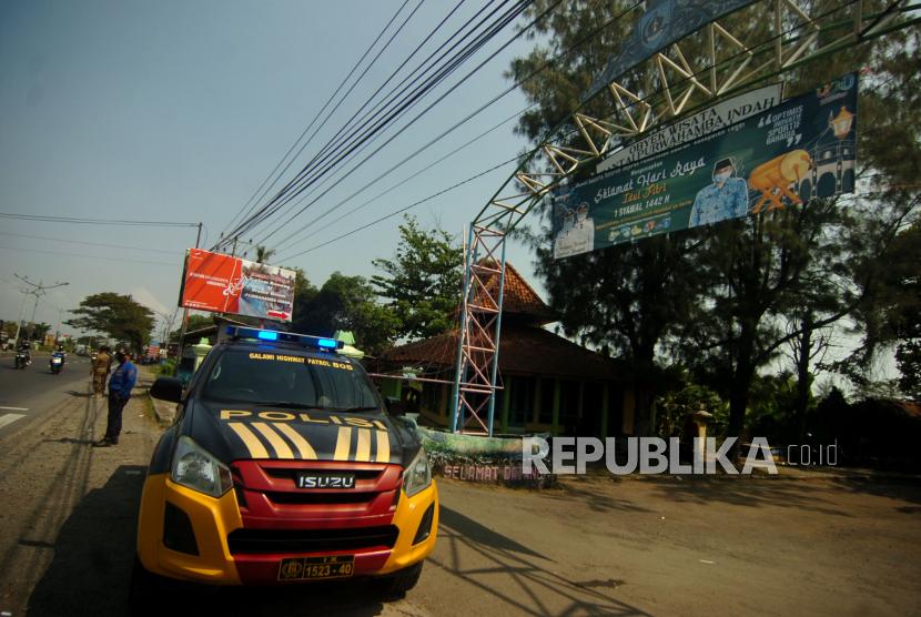 Kendaraan polisi menghalau pengunjung di pintu masuk obyek wisata Purwahamba Indah, Kabupaten Tegal, Jawa Tengah, Ahad (16/5/2021). Polres Tegal terpaksa menutup wisata Pantai Utara tersebut pada pukul 10.00 WIB karena membludaknya pengunjung pada libur Lebaran H+4, sedangkan kapasitas pengunjung hanya 30 persen dari 5.000 menjadi 1.500 orang.