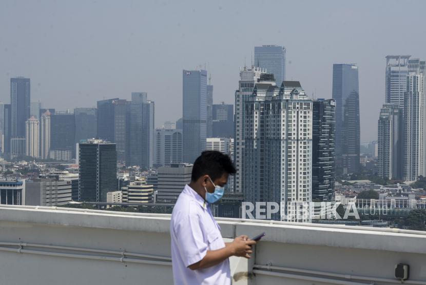 Petugas beraktivitas dengan latar belakang gedung-gedung bertingkat yang diselimuti polusi di Jakarta (ilustrasi)