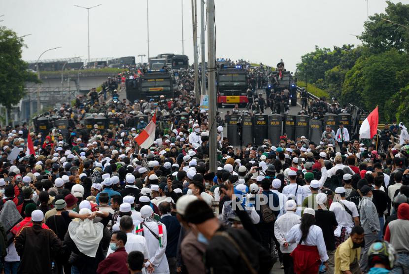 Petugas Kepolisian memblokade massa pendukung Habib Rizieq Shihab saat akan menuju Pengadilan Negeri Jakarta Timur di Jalan I Gusti Ngurah Rai, Jakarta, Kamis (24/6). Aksi massa tersebut dalam rangka mengawal sidang pembacaan vonis terhadap Habib Rizieq Shihab terkait kasus tes Swab di Rumah Sakit Ummi, Bogor.