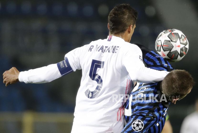 Josip Ilicic dari Atalanta, kanan, bertarung memperebutkan bola dengan Raphael Varane dari Real Madrid selama Liga Champions, babak 16 besar, pertandingan sepak bola leg pertama antara Atlanta dan Real Madrid, di Stadion Gewiss di Bergamo, Rabu, 24 Februari 2021.