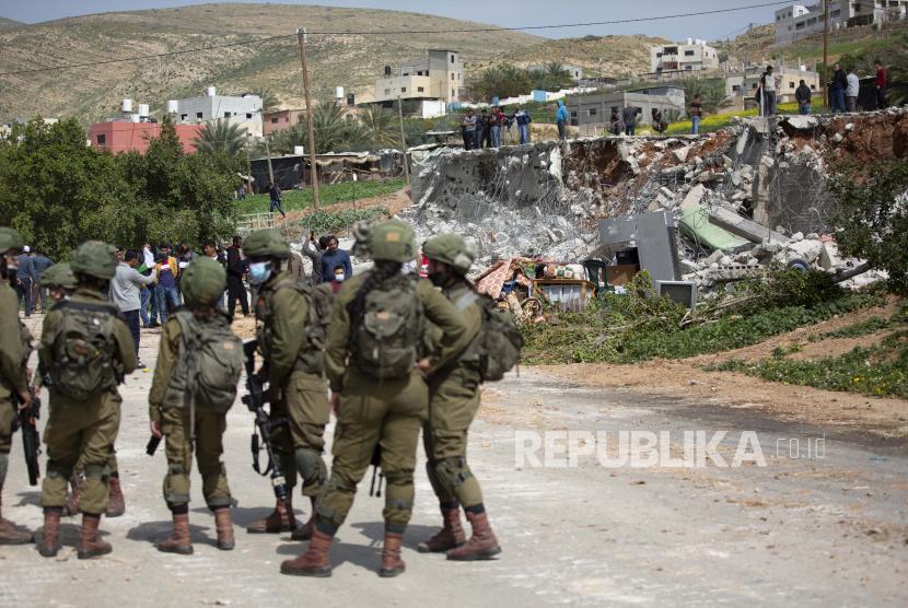 Tentara Israel berjalan melewati puing-puing rumah Palestina yang dibongkar oleh pasukan Israel karena dibangun tanpa izin, di desa Ain Shibli di Lembah Jordan Tepi Barat, Rabu, Maret. 10, 2021.