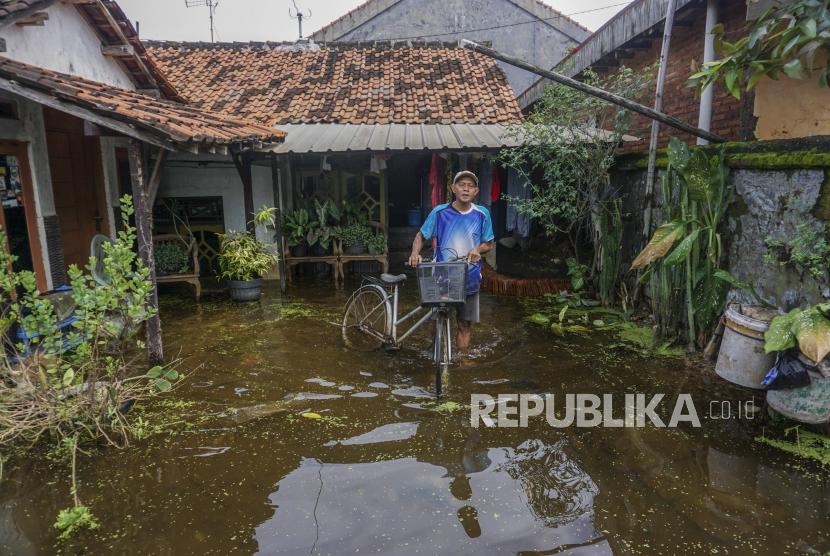 Warga mendorong sepedanya melewati genangan banjir di Tirto, Kabupaten Pekalongan, Jawa Tengah.