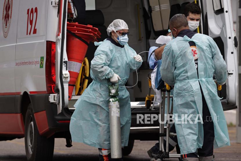 Petugas kesehatan mendorong pasien yang diduga menderita COVID-19 dengan tandu dari ambulans ke rumah sakit umum HRAN di Brasilia, Brasil, Kamis, 29 April 2021.