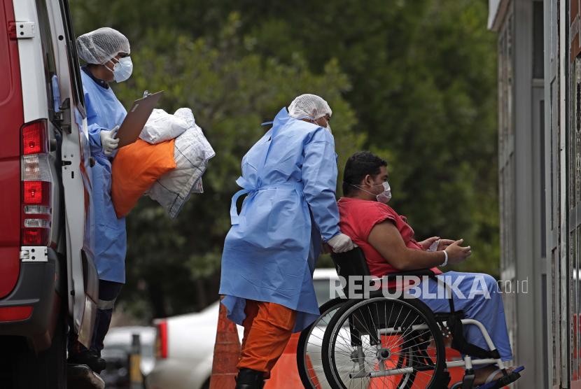 Brasil Laporkan 150 Ribu Kasus Covid-19 dalam Sehari. Petugas kesehatan kursi roda seorang pasien yang diduga menderita COVID-19 dari ambulans ke rumah sakit umum HRAN di Brasilia, Brasil, Kamis, 29 April 2021.