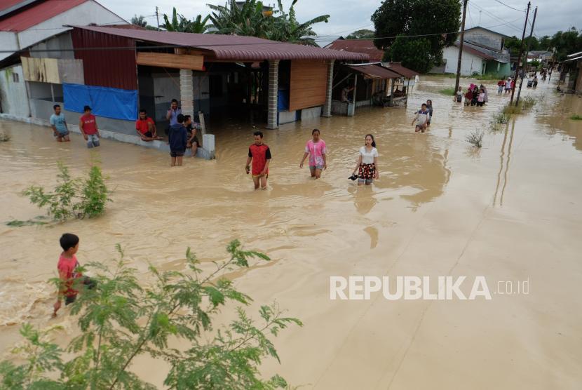 Warga melintasi banjir yang merendam pemukiman penduduk di Kecamatan Sunggal, Deli Serdang, Sumatera Utara, Jumat (4/12/2020). Banjir akibat meluapnya daerah aliran sungai Belawan menyebabkan ribuan rumah warga terendam.
