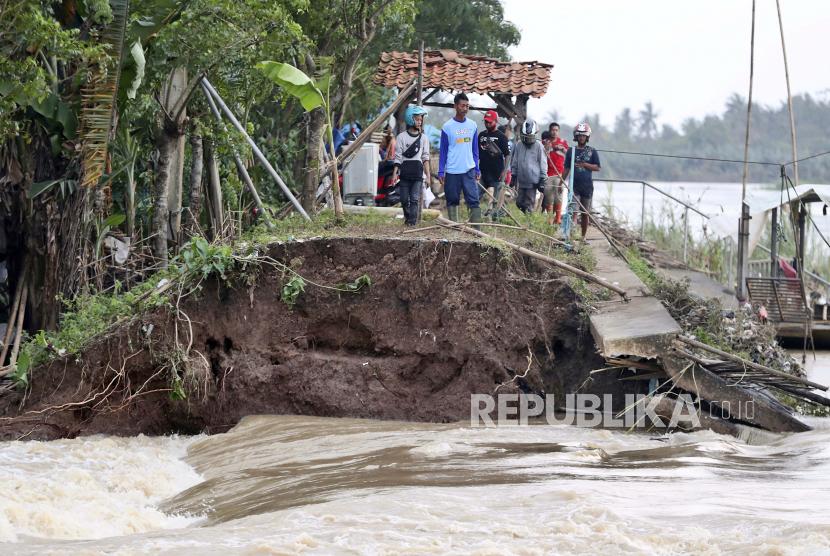 Warga memeriksa lokasi jebolnya tanggul Sungai Citarum yang menyebabkan banjir parah, di Bekasi, Indonesia, Senin, 22 Februari 2021. Ribuan warga dievakuasi di pinggiran ibu kota Indonesia di tengah banjir, kata pejabat Senin.