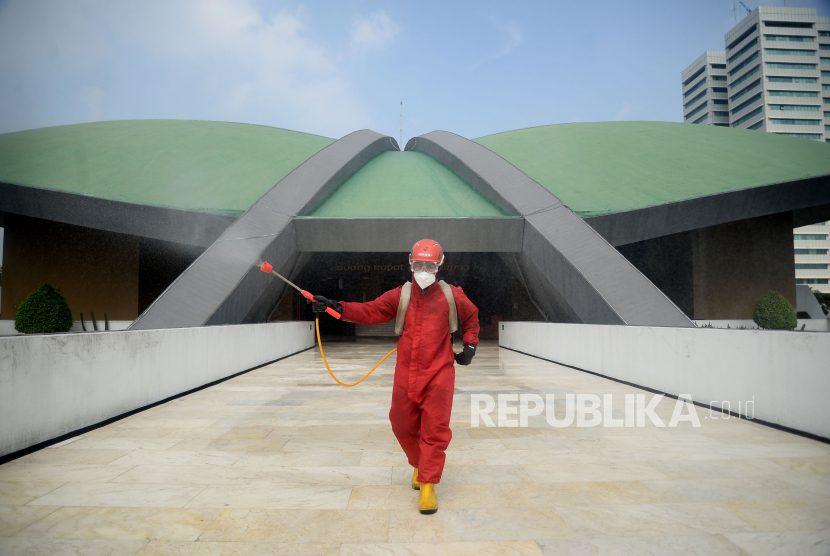 Petugas Pemadam kebakaran menyemprotkan cairan disinfektan di area kompleks gedung DPR/MPR RI, Jakarta.