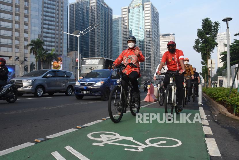 Gubernur DKI Jakarta Anies Baswedan (kiri depan) bersepeda saat berangkat kerja menuju kantornya.