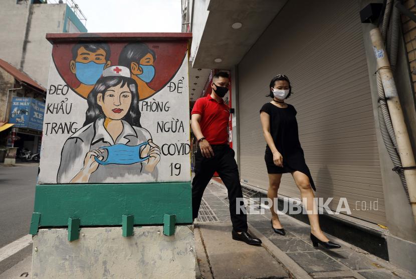 Orang-orang berjalan melewati kotak listrik yang dicat dengan tema COVID-19 di Hanoi, Vietnam, 07 Juni 2021.