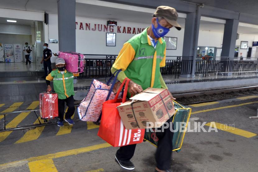 Porter membawa barang milik calon penumpang yang akan naik ke kereta api.