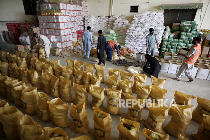 Polisi Islamabad Perketat Keamanan Selama Ramadhan. Foto: Pekerja dari kelompok amal Yayasan Alkhidmat Pakistan menyiapkan karung bahan makanan untuk dibagikan gratis di antara orang-orang yang membutuhkan untuk bulan puasa Ramadhan mendatang, di Islamabad, Pakistan, Minggu, 11 April 2021.