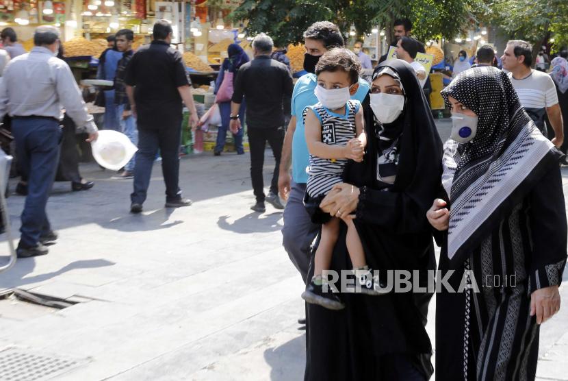 Orang Iran mengenakan masker wajah pergi berbelanja di sekitar bazaar besar Teheran di Teheran, Iran, 07 Juli 2020.