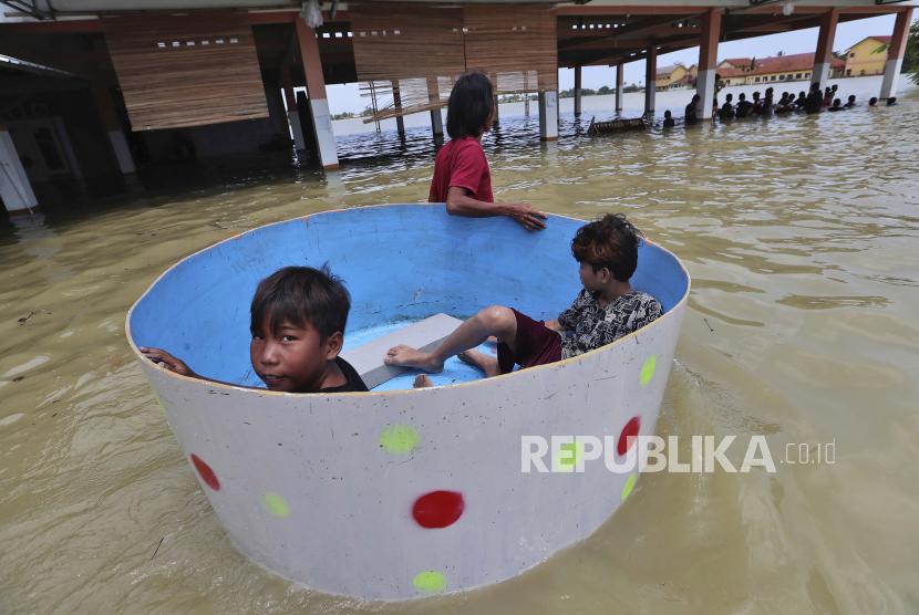 Anak-anak duduk di dalam bak saat banjir di Kecamatan Pebayuran, Kabupaten Bekasi, Jawa Barat, Senin, 22 Februari 2021, akibat tanggul Sungai Citarum jebol.