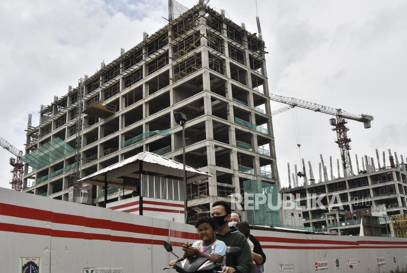 Sejumlah warga melintas disamping pembangunan Rumah Susun (Rumah Susun) PIK Pulogadung II, Jakarta Timur, Kamis (25/2/2021). Pemerintah provinsi DKI Jakarta menargetkan pembangunan 10 rusunawa selesai pada 2021 untuk mengatasi permasalahan pemukiman kumuh dan kebutuhan tempat tinggal.