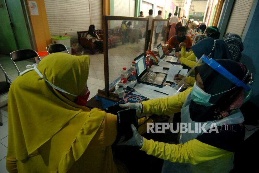 Petugas medis memeriksa kesehatan pedagang pasar sebelum melakukan vaksinasi (ilustrasi)