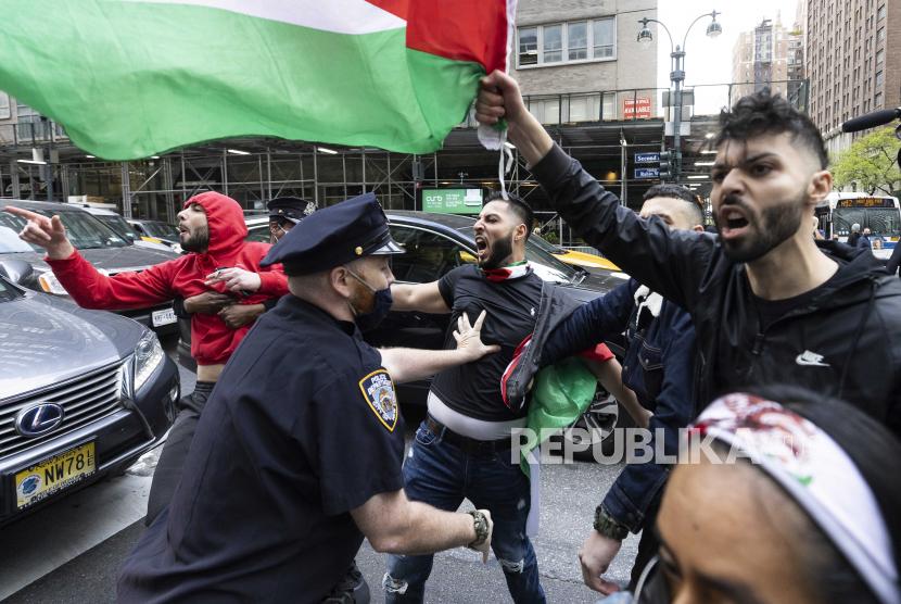 Petugas polisi mencoba untuk memisahkan pro-Palestina (kanan) dari demonstran pro-Israel selama unjuk rasa di dekat Konsulat Jenderal Israel di New York, New York, AS, 11 Mei 2021.