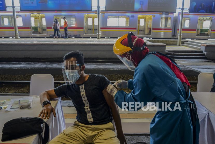 Tenaga kesehatan menyuntikan vaksin Covid-19 kepada penumpang kereta di Stasiun Bogor, Jawa Barat, Kamis (17/6). Vaksinasi di Stasiun Bogor yang merupakan tempat dengan interaksi mobilitas tinggi dan wilayah aglomerasi penyangga dari Kota Jakarta itu menyasar petugas dan pekerja di stasiun serta penumpang kereta. Republika/Putra M. Akbar