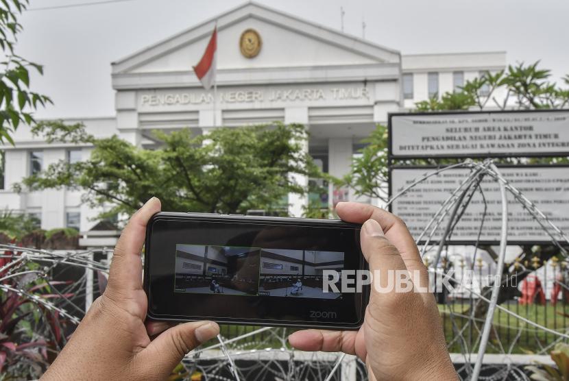 Layar telepon pintar menampilkan suasana sidang kasus pelanggaran protokol kesehatan dengan terdakwa Habib Rizieq Shihab yang digelar secara virtual di Pengadilan Negeri (PN) Jakarta Timur, Jakarta, Selasa (30/3/2021).