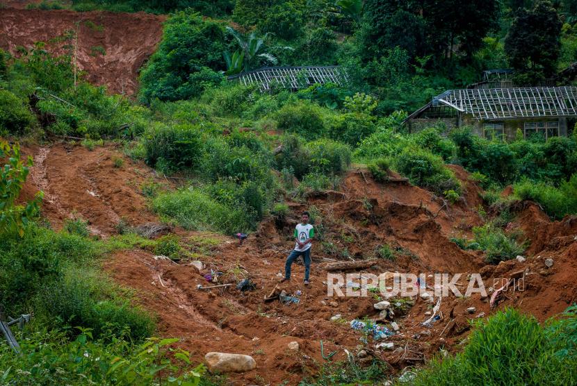 Seorang warga berdiri di atas bangunan rumah yang tertimbun material longsor di Kampung Cigobang, Lebak, Banten, Ahad  (3/1/2021). Pascabencana banjir bandang dan longsor yang terjadi di Kampung Cigobang pada Rabu (1/1/2020) mengakibatkan 154 kepala keluarga (KK) memilih meninggalkan kampung tersebut karena khawatir potensi bencana akibat stuktur tanah yang labil terjadi kembali.
