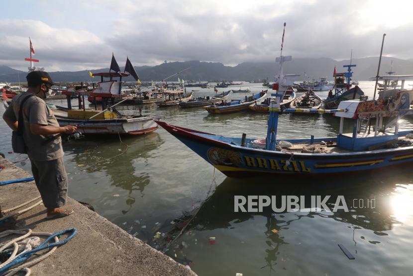Pengunjung memancing ikan dengan latar belakang perahu nelayan yang ditambatkan di Pantai Popoh, Tulungagung, Jawa Timur, Selasa (1/6/2021). Sejak lima hari terakhir nelayan di daerah itu terpaksa tidak melaut karena tingginya gelombang di perairan pantai selatan Jawa.
