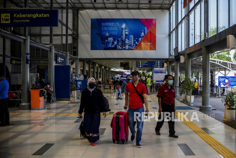 Sejumlah penumpang kereta berjalan membawa koper di Stasiun Pasar Senen, Jakarta, Kamis (8/7). PT Kereta Api Indonesia (Persero) atau KAI memastikan akan mendukung kebijakan pemerintah selama Pemberlakuan Pembatasan Kegiatan Masyarakat (PPKM) Level 4. Salah satunya mengenai pembatasan kapasitas penumpang.