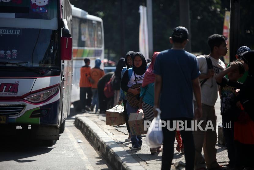 Pemudik berjalan seusai turun dari bus di Terminal Kampung Rambutan, Jakarta, Senin (18/6).