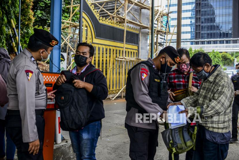 Sejumlah anggota kepolisian memeriksa tas yang dibawa oleh pengunjung di Mapolda Metro Jaya, Jakarta, Kamis (1/4). Polda Metro Jaya memperketat akses masuk ke wilayah tersebut dengan melakukan pemeriksaan barang bawaan pengunjung dan pengamanan menggunakan anggota bersenjata untuk mengantisipasi ancaman teror pasca kejadian penyerangan di Mabes Polri. Republika/Putra M. Akbar