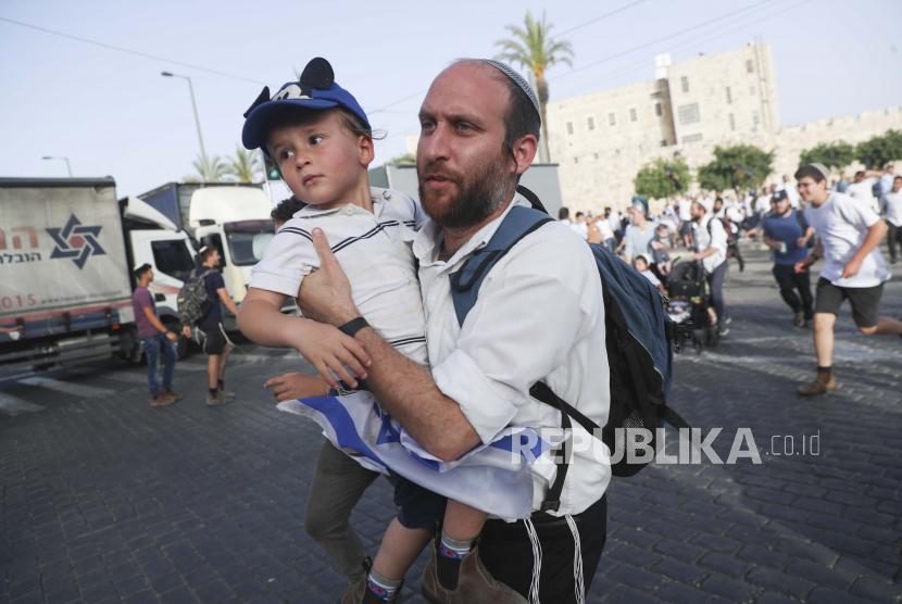 Orang Israel lari ke tempat penampungan saat sirene serangan udara berbunyi selama pawai Hari Yerusalem, di Yerusalem, Senin, 10 Mei 2021.