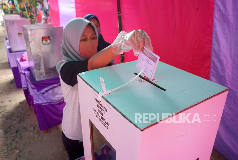 [Ilustrasi] Seorang warga memasukkan surat suara ke dalam kotak suara.