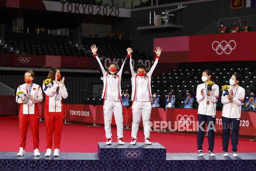 Peraih medali emas Greysia Polii (kiri) dan Apriyani Rahayu (kanan) bereaksi selama upacara pemberian penghargaan Bulutangkis Ganda Putri di Olimpiade Tokyo 2020 di Musashino Forest Sports Plaza di Chofu, Tokyo, Jepang, 02 Agustus 2021.