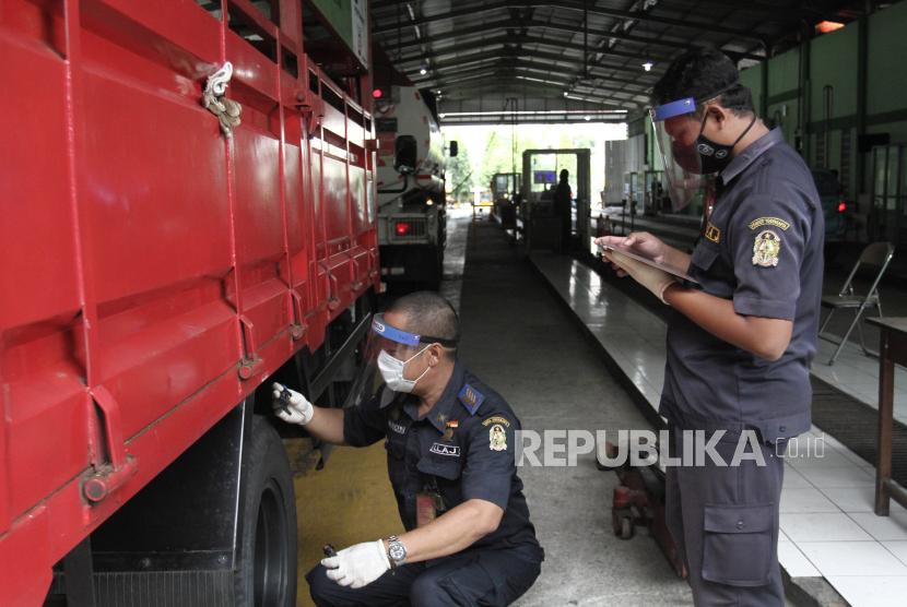 Petugas melakukan uji kir berkala kendaraan.