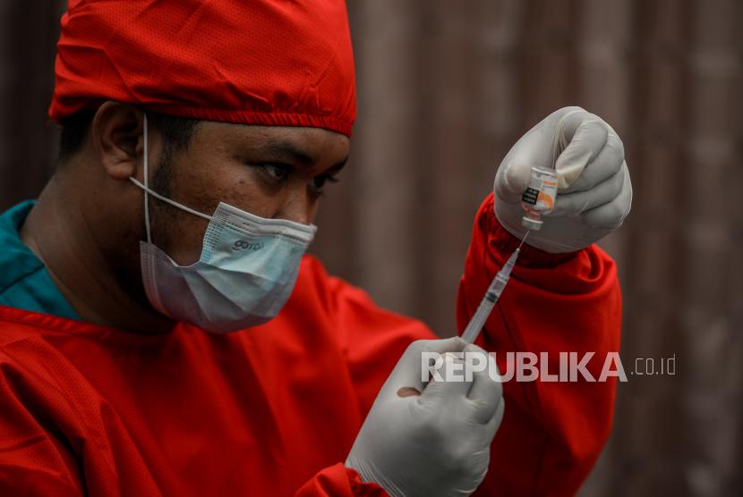 Tenaga kesehatan mengisi tabung suntikan dengan cairan vaksin Covid-19 sebelum disuntikan kepada warga di Universitas Nasional, Jakarta, Senin (26/7). Menurut Gubernur DKI Jakarta Anies Baswedan mengklaim sebanyak 7 juta orang di DKI Jakarta  telah menerima vaksin Covid-19 dosis pertama, sedangkan berdasarkan data Dinkes DKI Jakarta jumlah penerima vaksin dosis kedua pada 24 Juli 2021 mencapai 2.191.407 orang atau 24,9 persen. Republika/Thoudy Badai
