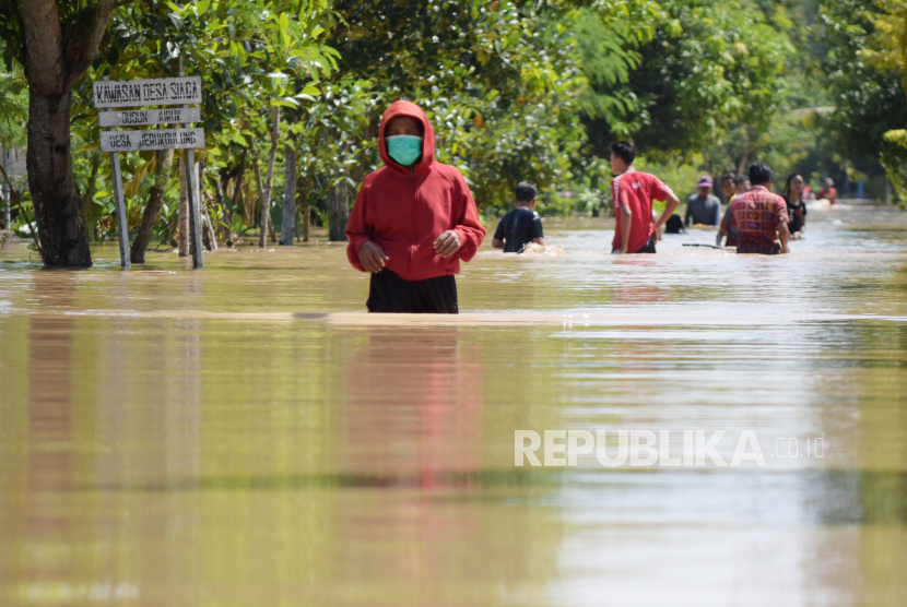 Sejumlah warga menerobos jalan yang terendam banjir di Desa Jerukgulung, Balerejo, Kabupaten Madiun, Jawa Timur, Kamis (15/4/2021). Sejumlah desa di empat kecamatan di Kabupaten Madiun terendam banjir luapan Sungai Jeroan akibat hujan deras Rabu (14/4) sore hingga malam.