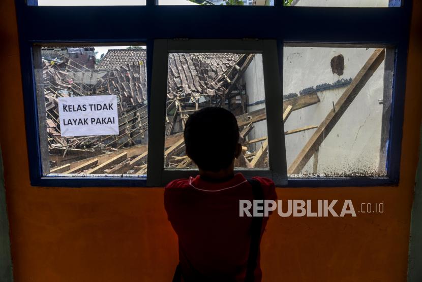 Warga melihat kondisi ruangan kelas yang ambruk di SDN Otista, Baranangsiang, Kota Bogor, Jawa Barat, Jumat (17/9). Sebanyak dua kelas ambruk pada bagian atap bangunan yang sudah tidak layak digunakan untuk kegiatan belajar mengajar karena kondisi kayu yang lapuk.