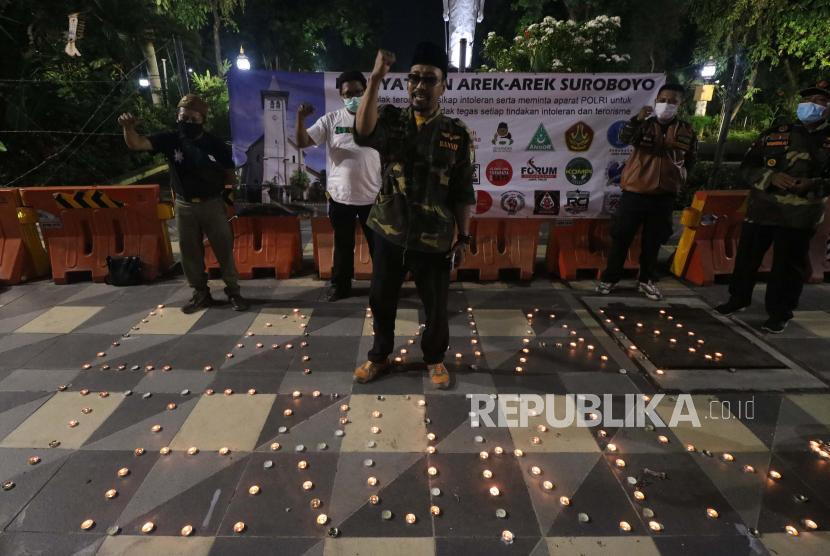 Warga melakukan aksi di Taman Apsari, Surabaya, Jawa Timur, Selasa (30/3/2021). Aksi itu mengecam tindakan terorisme bom bunuh diri yang terjadi di Gereja Katedral Makassar, Sulawesi Selatan pada Minggu (28/3/2021).