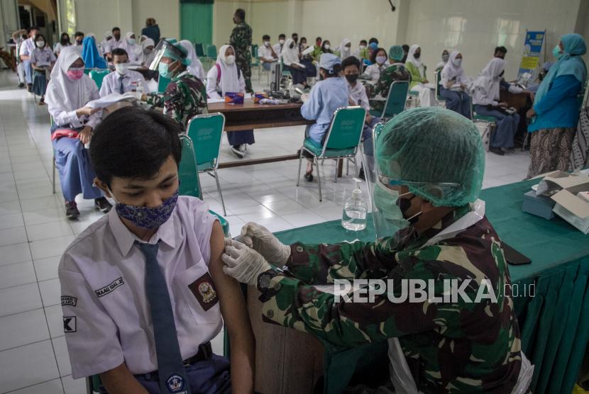 Petugas medis menyuntikan vaksin kepada pelajar saat Vaksinasi COVID-19 di SMA Negeri 1 Surakarta, Solo, Jawa Tengah