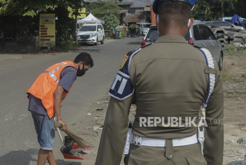 Petugas Satpol PP  memberi sanksi kerja sosial kepada warga yang melanggar protokol kesehatan (ilustrasi).