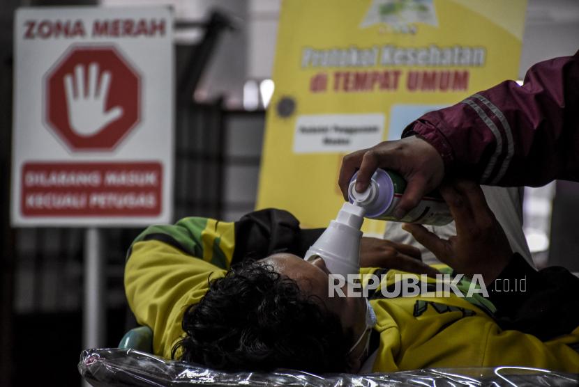 Keluarga pasien memberikan alat bantu pernapasan ke pasien sambil menunggu ruangan rawat inap di area ruang Instalasi Gawat Darurat (IGD) Rumah Sakit Dokter Hasan Sadikin (RSHS), Kota Bandung, Ahad (13/6). Berdasarkan data dari Pusat Informasi dan Koordinasi Covid-19 Provinsi Jawa Barat (Pikobar) pada (12/6), tingkat keterisian tempat tidur atau Bed Occupancy Rate (BOR) rumah sakit yang melayani Covid-19 dan tidak melayani Covid-19 telah mencapai 67,31 persen dengan rincian sebanyak 9.120 dari total 13.550 tempat tidur telah terisi.