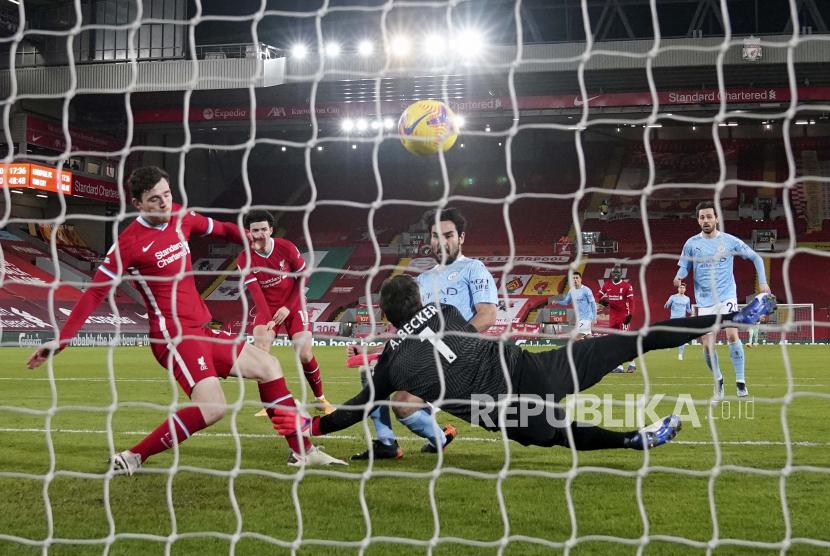 Ilkay Gundogan dari Manchester City, tengah, mencetak gol pembuka melewati kiper Liverpool Alisson selama pertandingan sepak bola Liga Utama Inggris antara Liverpool dan Manchester City di Stadion Anfield, Liverpool, Inggris, Minggu, 7 Februari 2021.