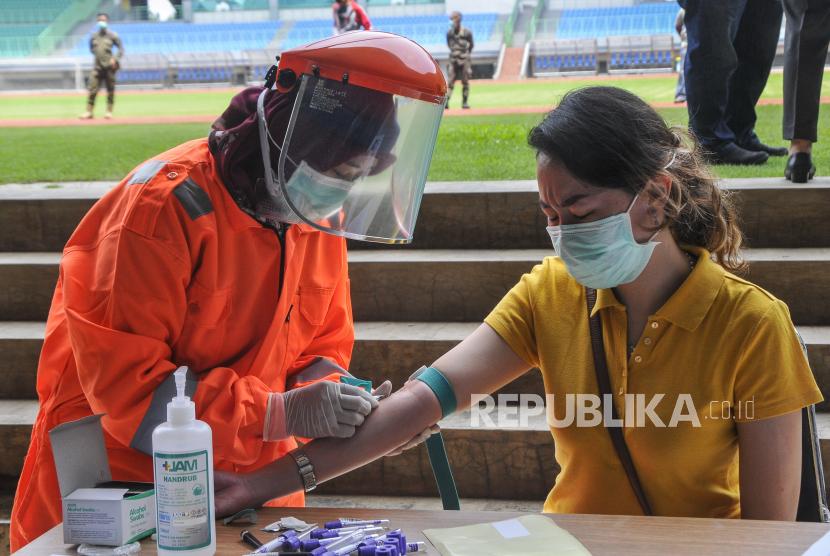 Petugas medis mengecek kesehatannya dengan mengambil sampel  darah dengan metode rapid test (pemeriksaan cepat) di Stadion Patriot Candrabhaga, Bekasi, Jawa Barat, Rabu (25/3/2020). Pemeriksaan yang dilakukan khusus tenaga medis di Bekasi guna memutus mata rantai penyebaran virus COVID-19